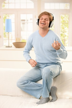 imitating: Young man imitating playing on guitar while listening to music on headphones with eyes closed, laughing. Stock Photo