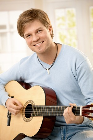 Portrait of handsome guy playing guitar, looking at camera, smiling. photo