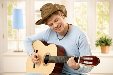 Young man wearing hat playing guitar at home, smiling. photo