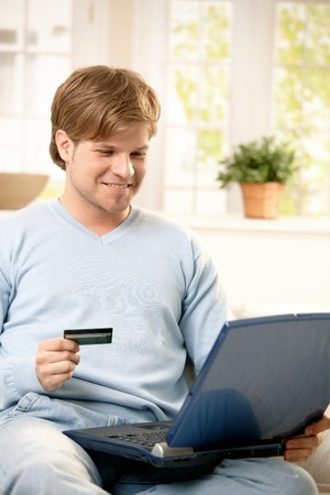 Smiling man shopping online with laptop computer in lap, holding credit card. photo
