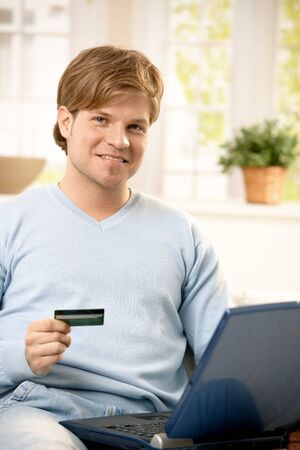 Portrait of young man paying with credit card online, holding computer, smiling at camera. Stock Photo - 7249405