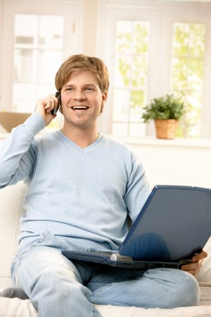 Handsome young man sitting on sofa, talking on mobile phone, smiling, having laptop computer. photo