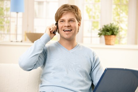 Smiling young man using cellphone, holding computer, sitting on couch in living room. photo