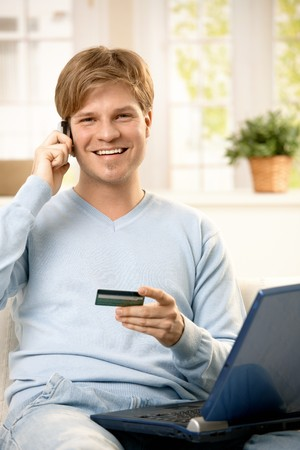 Smiling man talking on mobile phone, holding creditcard, sitting on couch with laptop computer, looking at camera photo