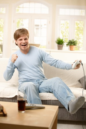 Happy guy playing computer game at home, sitting on living room couch, laughing. photo