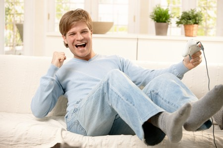 Happy guy playing computer game, holding controller, laughing on living room sofa. photo