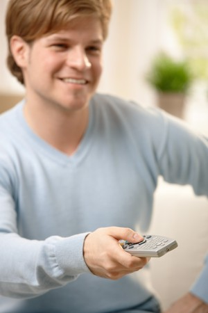 Smiling blond guy using remote control, focus on hand. photo