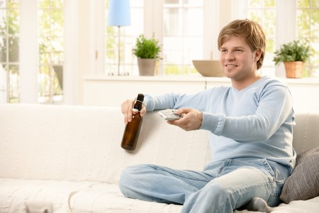enjoy space: Man relaxing on living room sofa, using remote control, having beer, smiling. Stock Photo