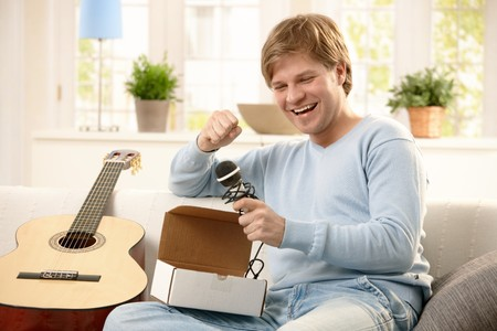 Happy guy getting present, opening box of microphone, sitting on couch with guitar. Stock Photo - 7249378