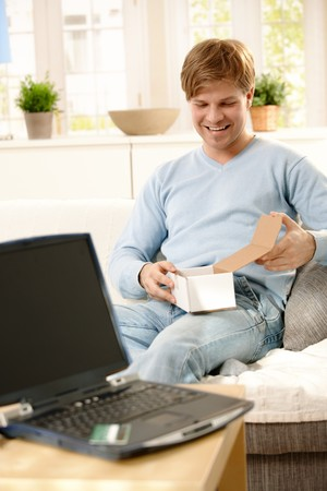 Young man  in focus opening box sitting on couch, laptop computer and credit card on table, using for online shopping. photo