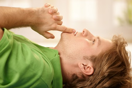 concentrating: Young man lying on floor, concentrating with hands put together, finger put at lips, looking up, thinking in closeup. Stock Photo