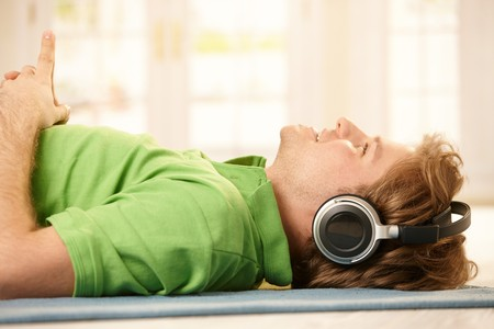 listening back: Young man lying on floor wearing headphones, pointing up, smiling.