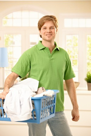 Portrait of smiling man holding a basket of clothes to wash, standing in living room, looking at camera. photo