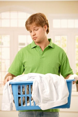 Young guy bored of housework holding a basket of clothes to do washing. Stock Photo - 7249393