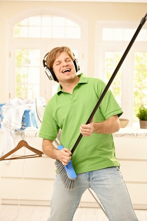 Smiling man singing with headphones, imitating playing guitar on broom at home.