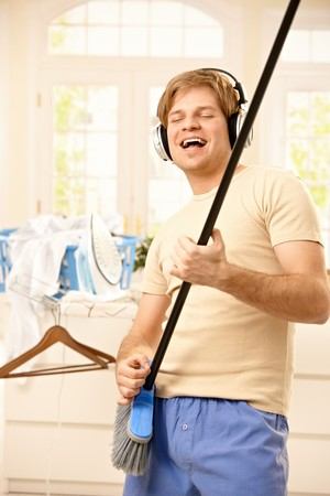 Happy young man having fun at housework, wearing headphones imitating guitar play on broomstick, smiling at home. photo