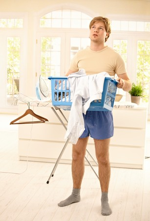 Tired young guy standing at home fed up with housework, looking up, holding washing basket. photo