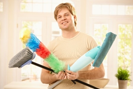 Young man smiling confidently with cleaning tools, holding mop, broom and flannel. photo
