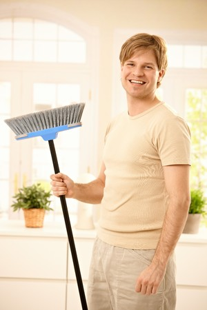 Happy guy laughing at camera, holding broomstick standing in living room. photo