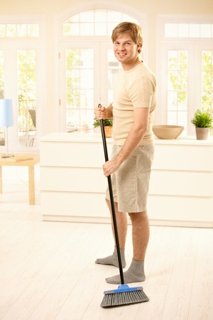 Smiling guy sweeping the floor in living room, looking at camera, standing.