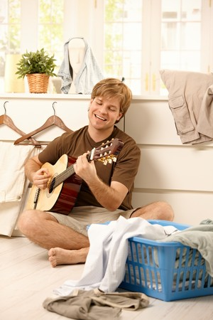 Cheerful guy singing and playing guitar sitting on floor of living room instead of doing housework, washing laundry. photo