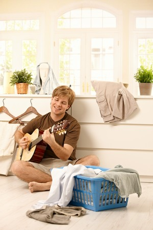 Happy young man singing and playing guitar sitting on floor full of laundry instead of housework. photo