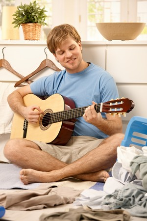 Lazy young guy playing guitar sitting on floor instead of doing housework. photo