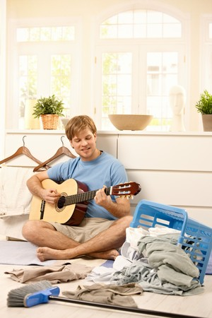Lazy young guy playing guitar sitting on floor instead of washing laundry or sweeping. photo