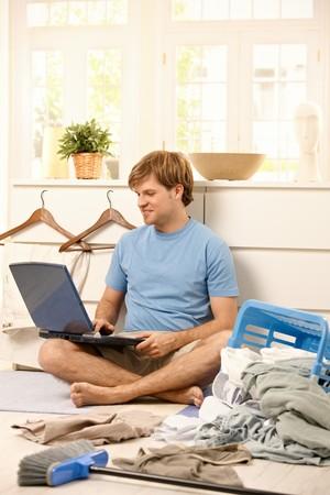 habitacion desordenada: Hombre perezosa, navegaci�n por internet en equipo port�til sentada en el suelo de la sala de estar en lugar de lavander�a de lavado
