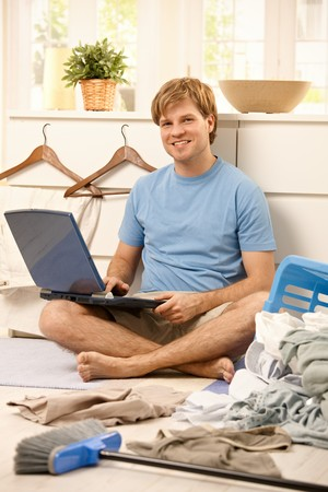 Lazy guy sitting with laptop computer instead of cleaning.  photo
