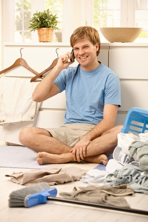 Happy guy sitting on living room floor talking on cellphone, looking at camera,  instead of doing the laundry or cleaning.     photo