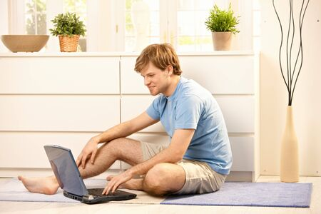 Young man browsing internet on laptop computer, typing on keyboard sitting on living room floor. Stock Photo - 7249339