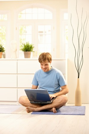 Young guy looking at laptop computer sitting on floor at home. Stock Photo - 7249300