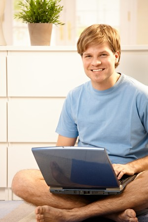 Portrait of young man with laptop computer sitting o n floor at home.  Stock Photo - 7249344