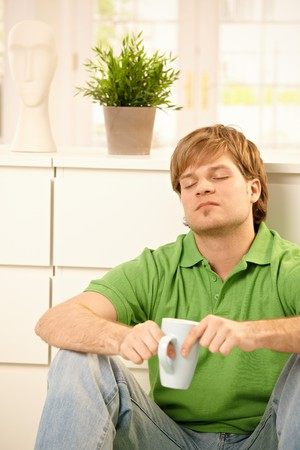 Handsome young man sitting at home, holding coffee mug, thinking with closed eyes. photo