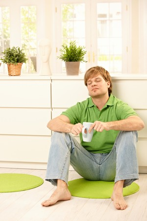 Handsome young man sitting on living room floor, having coffee, smiling  with closed eyes. photo