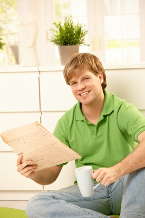 Handsome young man reading newspaper and drinking coffee, smiling  at camera at home. Stock Photo - 7249366