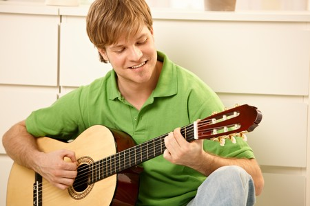 Goodlooking guy playing guitar at home.  photo