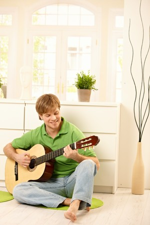 Goodlooking guy playing guitar in bright living room. photo