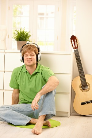 Goodlooking guy sitting on bright living room floor next to guitar, listening to music via headphones, smiling with closed eyes. photo