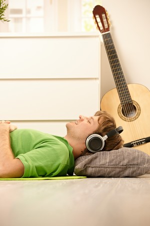 Goodlooking guy lying on living room floor, listening to music via headphones, smiling with closed eyes. Stock Photo