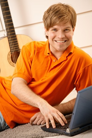 Portrait of handsome man using laptop computer on living room floor, smiling at camera. photo