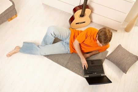 high angles: Young man lying on living room floor next to guitar, using computer, taken from high angle view.