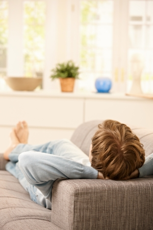 Man lying on couch relaxing at home in sunny living room. photo