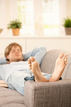 Man lying on couch relaxing with bare feet up at home in sunny living room. photo