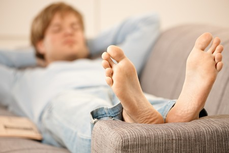 napping: Man lying on back on sofa in  bright living room, focus on bare feet.