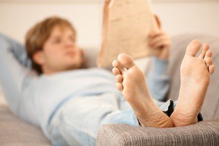 Man lying on back on sofa reading newspaper, focus on bare feet. photo