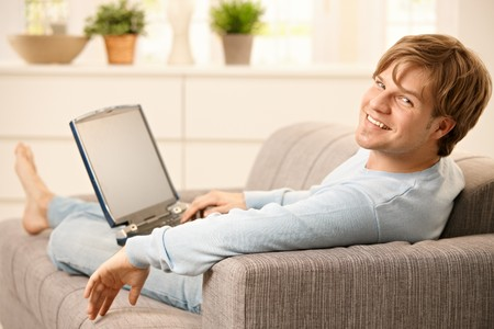 Man sitting with laptop computer on sofa  with feet up in living room, looking back at camera, smiling. photo