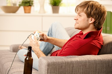 Young man sitting on sofa playing computer game, smiling, photo