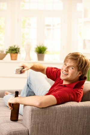 Young man sitting on sofa holding remote control and beer, smiling at camera. Stock Photo - 7249411
